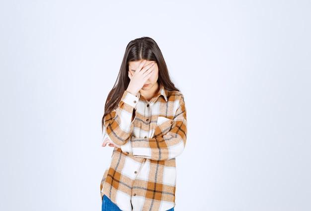立って白い壁に顔を覆っている若い女性。