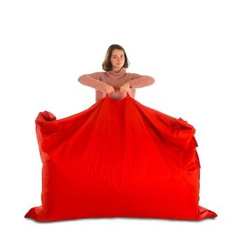 居間または白で隔離された他の部屋のための赤い長方形のビーンバッグソファチェアを立って保持している若い女性