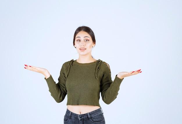 若い女性が立って、何かがうまくいかないように手を見せている。