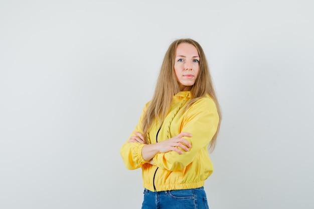 Молодая женщина стоя скрестила руки в желтой куртке бомбардировщика и голубых джинсах и выглядела элегантно, вид спереди.