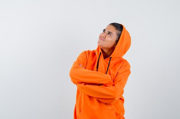 Giovane donna in piedi con le braccia incrociate, distoglie lo sguardo con una felpa arancione e sembra raggiante
