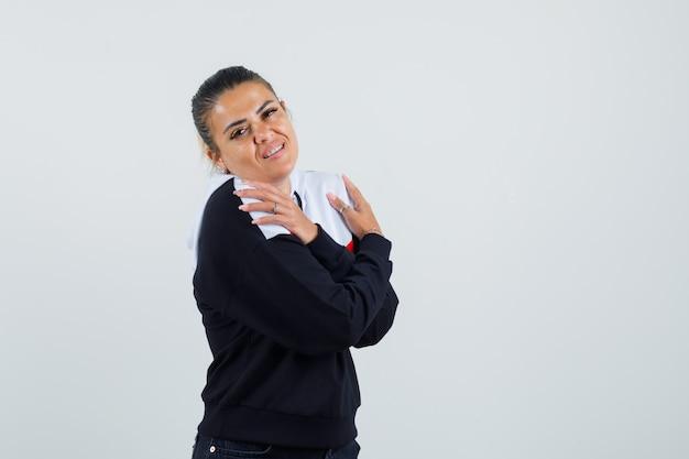 Giovane donna in piedi con le braccia incrociate e guardando sopra le spalle in maglione e jeans neri e sembra carina. vista frontale.