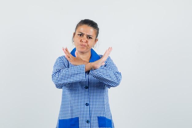 Giovane donna in piedi con le braccia incrociate, mostrando il gesto di restrizione in camicia del pigiama a quadretti blu e guardando serio, vista frontale.