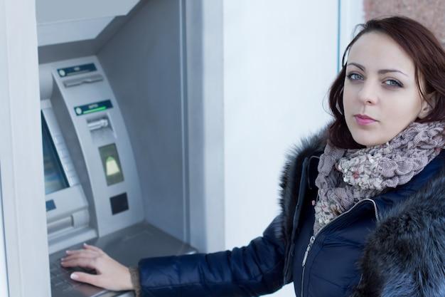 은행 밖 Atm 기계에 서서 자동 입출금기에서 돈을 인출하기 위해 기다리는 젊은 여성 프리미엄 사진