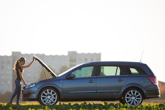 Молодая женщина, стоя на машине, глядя под поп капот