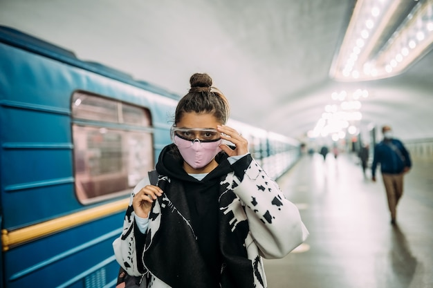 医療用防護マスクを着て駅に立つ若い女性