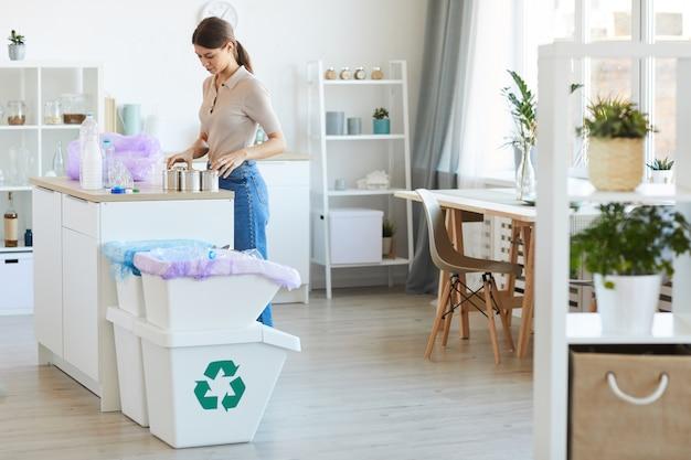 台所のテーブルに立って、ペットボトルと缶をリサイクルする若い女性