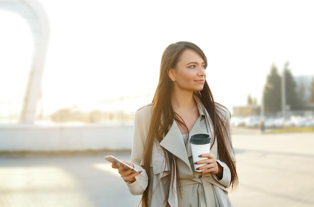 이동 커피를 마시고 휴대 전화를 사용하는 거리에 서있는 젊은 여자
