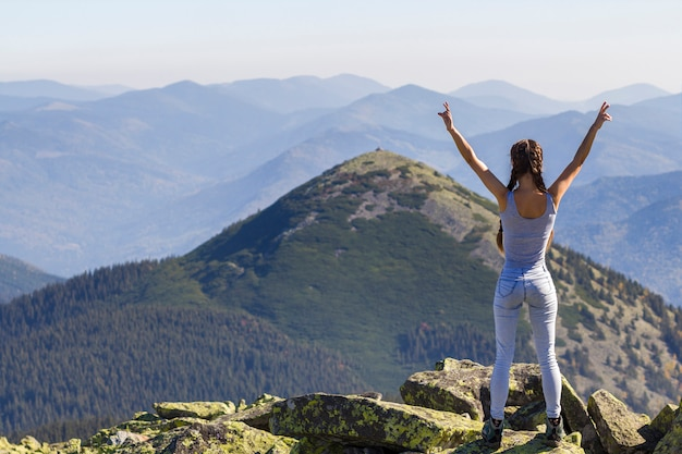 Young woman standing on big rocks in mountains lifting hands meeting a raising sun.