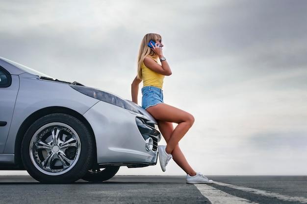 道路で壊れた車のそばに立って、スマートフォンの呼び出し支援を使用して若い女性。車の技術者に連絡するか、助けが必要な路上で車を分解する際に携帯電話を使用している女の子。