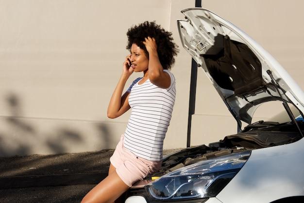 若い女性が壊れた車で立って、援助のために電話をかける