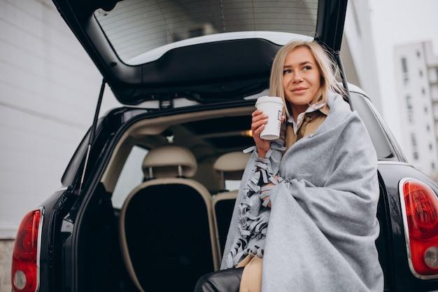 Молодая женщина стоит у своей машины и пьет кофе
