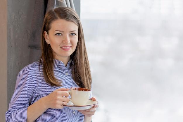 Молодая женщина, стоя у окна с чашкой чая, кофе. улыбающаяся привлекательная девушка.