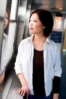 Young woman standing by window, smiling