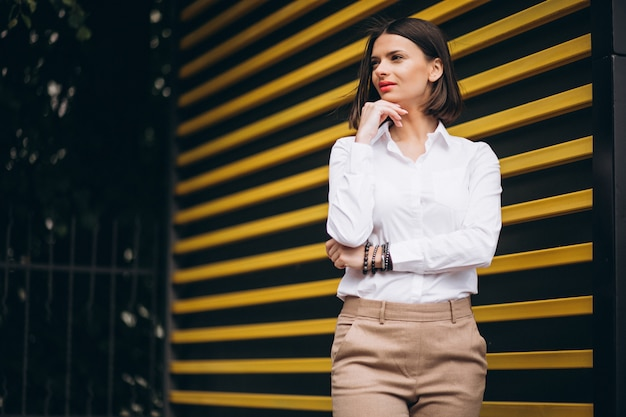 Young woman standing by the yellow wall