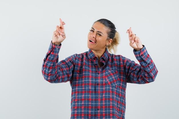 Giovane donna in piedi dita incrociate e con la lingua fuori in camicia a quadri e guardando felice. vista frontale.