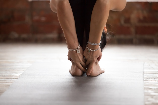Young woman in standing forward bend pose