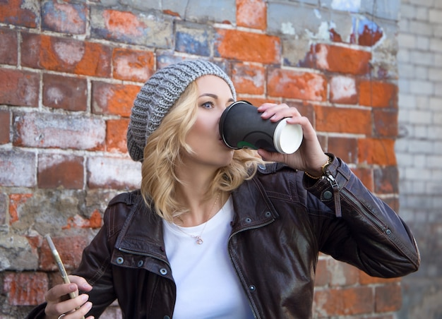 Young woman standing in front of brick wall drinking coffee