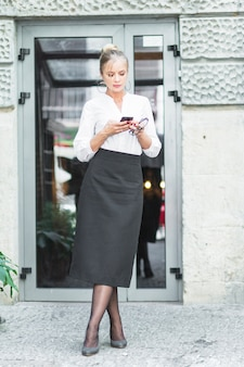 Young woman standing in front of glass door using cellphone