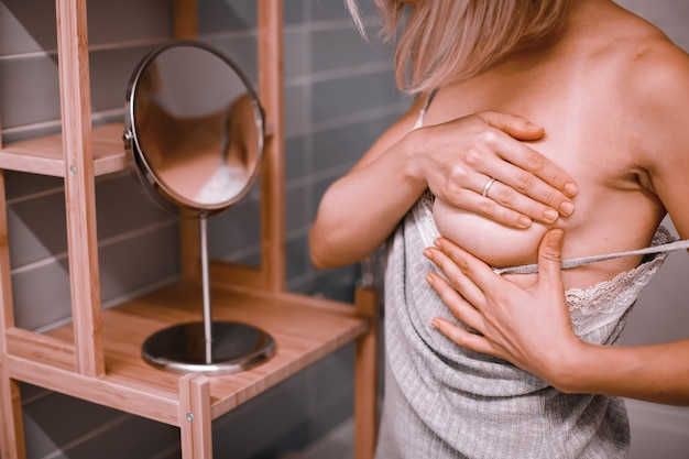 Young woman standing in front of the mirror, checking her breast while self exam. breast cancer awareness. how do i check breast concept.