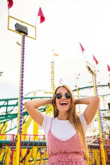 Young woman standing in front of roller coaster laughing