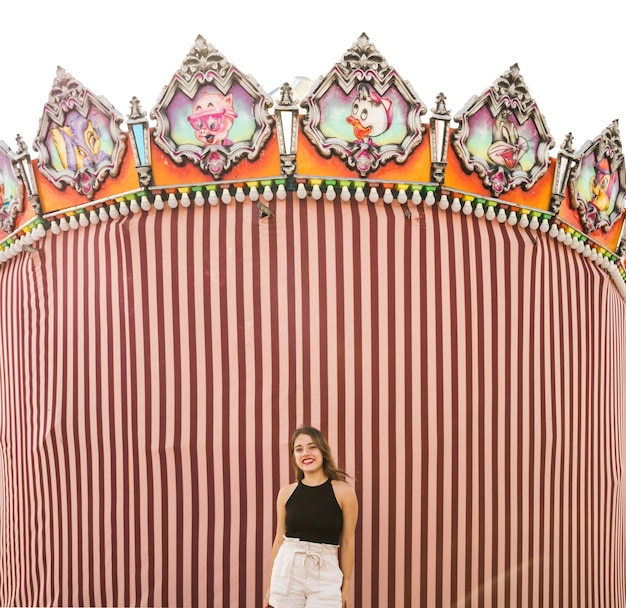 Young woman standing in front of tent at amusement park