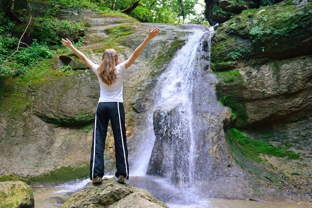 Young woman standing in front of waterfall with her hands raised