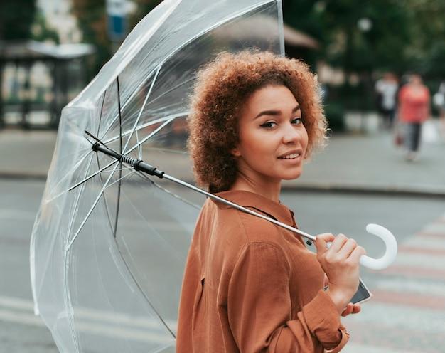 Giovane donna in piedi sotto il suo ombrello