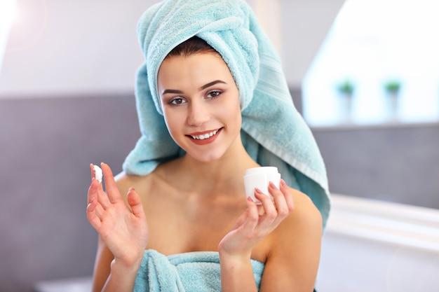 Молодая женщина, стоящая в ванной и применяющая крем для лица утром