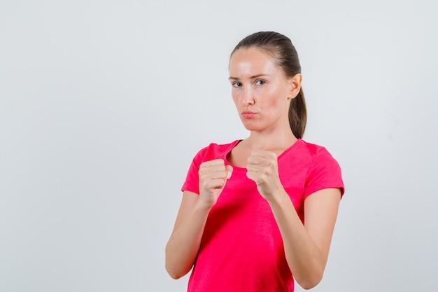 Молодая женщина, стоящая в позе боксера в розовой футболке и серьезно выглядящая. передний план.