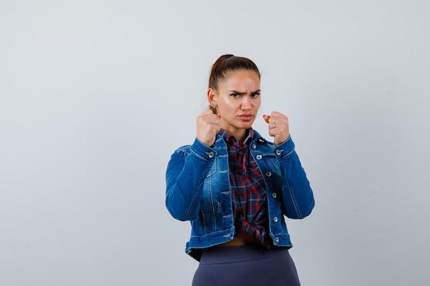Молодая женщина, стоящая в бою, позирует в клетчатой рубашке, джинсовой куртке и выглядит уверенно, вид спереди.