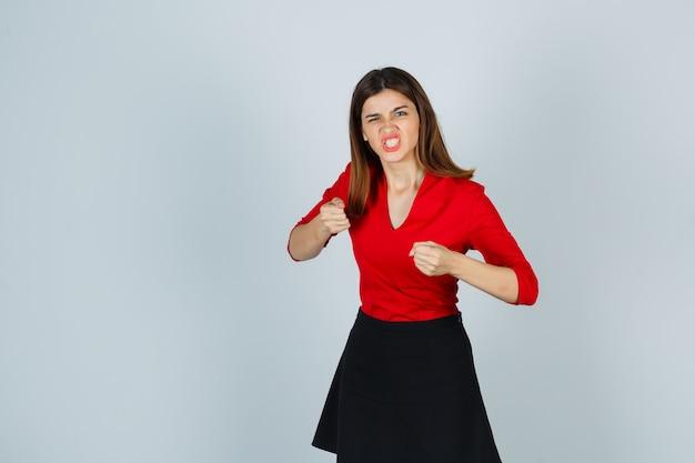 Молодая женщина, стоящая в позе боя в красной блузке