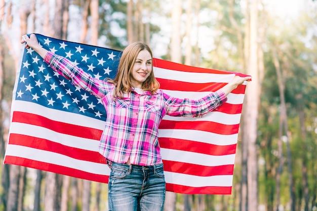 森の中に立っているとアメリカの国旗を保持している若い女性