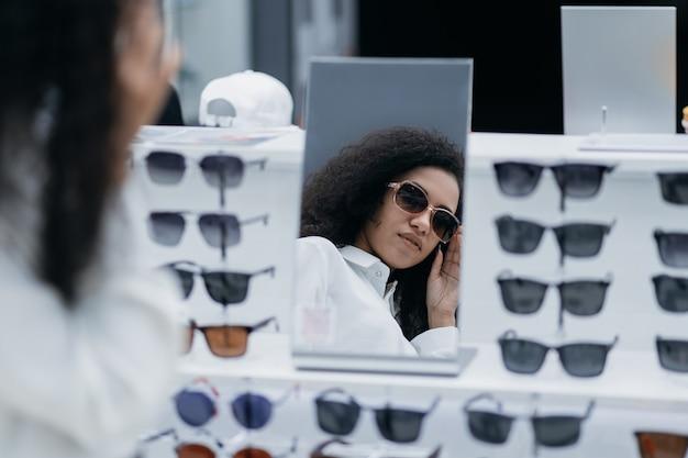 Молодая женщина, стоящая перед зеркалом в магазине оптометрии