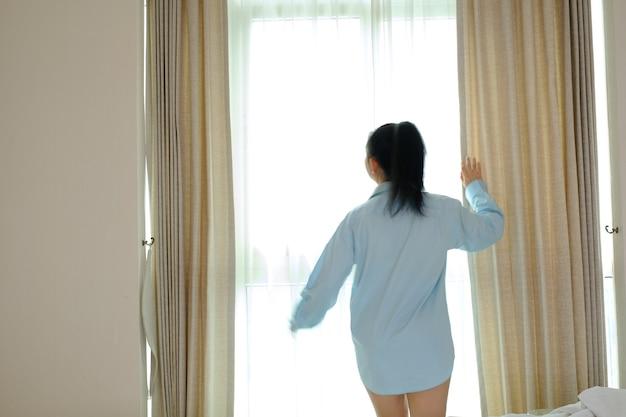 外を見て寝室の窓の前に立っている若い女性