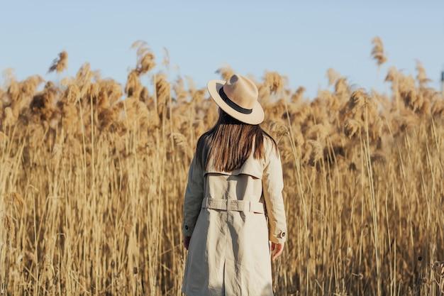 晴れた日の田舎の黄金の葦畑に立っている若い女性