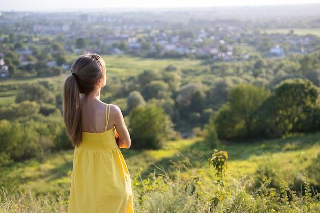 夕方の自然の中で夕日の景色を楽しむ緑の野原に立っている若い女性。リラクゼーションと瞑想の概念。