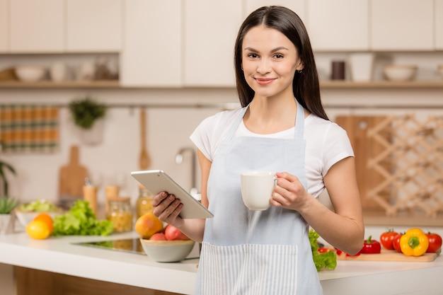 Молодая женщина, стоя на кухне с планшетным компьютером и глядя рецепты. улыбаясь, глядя в камеру, с чашкой чая