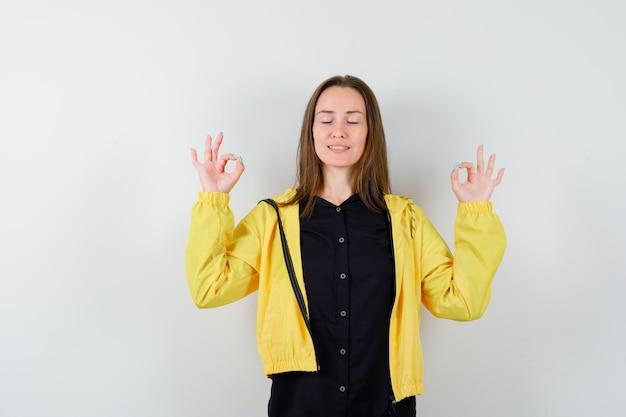 Молодая женщина, стоя в позе медитации