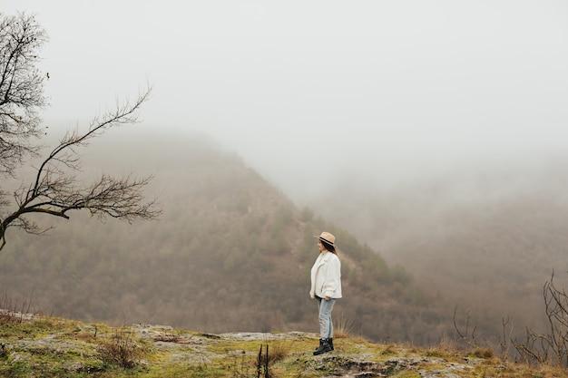 하얀 안개와 함께 아침 산에 서서 목가적 인 자연의 경치를 즐기는 젊은 여자.