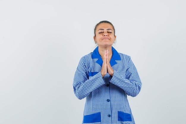 青いギンガムチェックのパジャマシャツで祈りのポーズで立って、リラックスして見える若い女性、正面図。