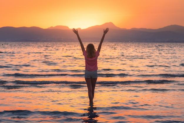 Молодая женщина, стоящая в море с волнами на песчаном пляже на фоне гор и оранжевого неба на закате летом