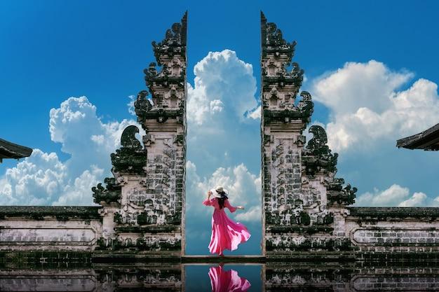 Молодая женщина стоит у ворот храма лемпуянг лухур на бали, индонезия. винтажный тон