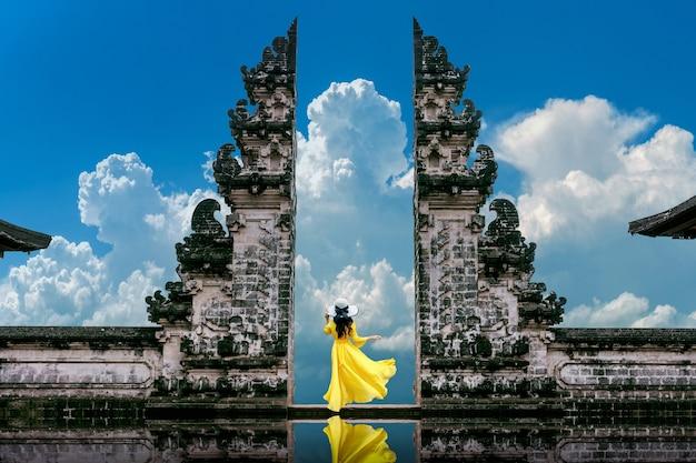 インドネシア、バリ島のlempuyangluhur寺院の寺院の門に立っている若い女性。ヴィンテージトーン