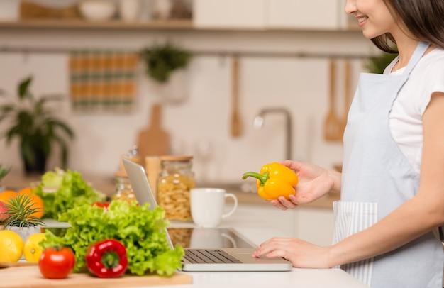 ノートパソコンとキッチンに立っている若い女性