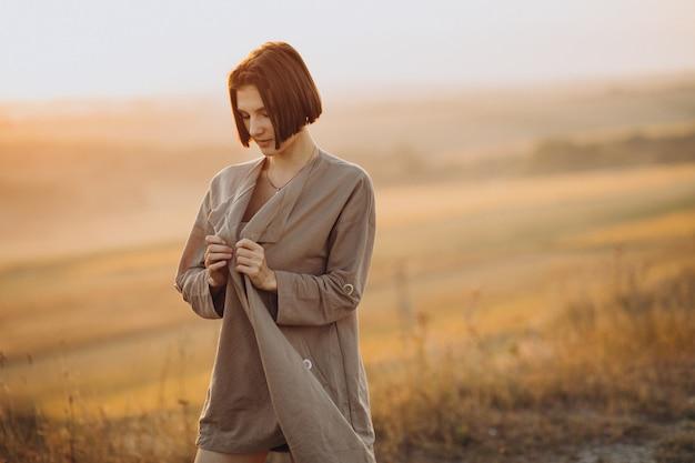 夕日の草原に立っている若い女性