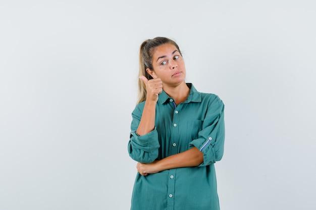 Молодая женщина, стоящая в позе мышления и указывая указательным пальцем влево в зеленой блузке, задумчивая