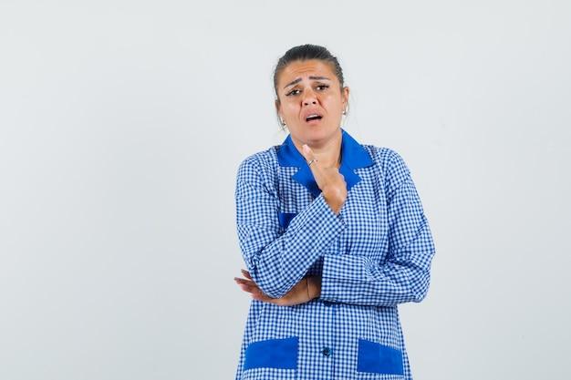 젊은 여자는 생각 포즈에 서서, 파란색 깅엄 파자마 셔츠에 주먹을 움켜 쥐고 스트레스를 찾고 있습니다. 전면보기.