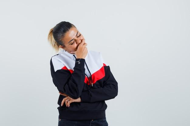 젊은 여자는 생각 포즈에 서, 스웨터와 검은 색 청바지에 손으로 입을 덮고 소심한 찾고. 전면보기.