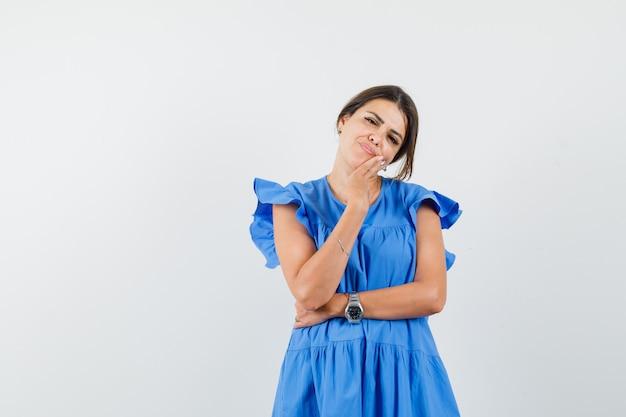 青いドレスを着てポーズを考えて立っている若い女性